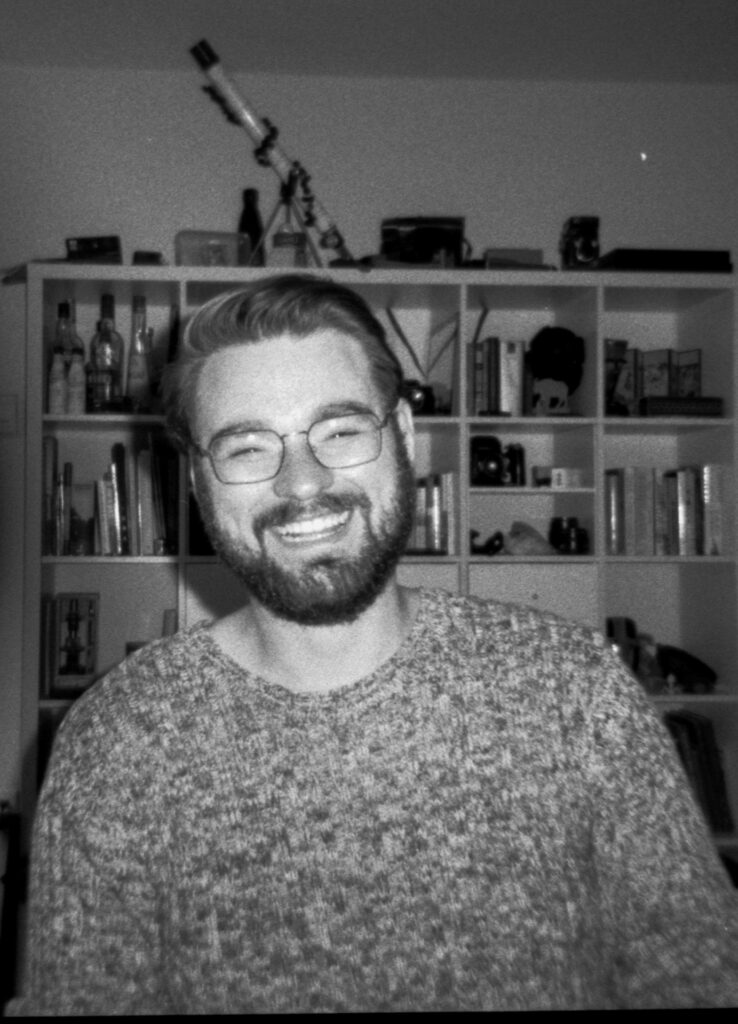 A B&W portrait of a man, bearded haphazardly smiling in front of a weird shelf