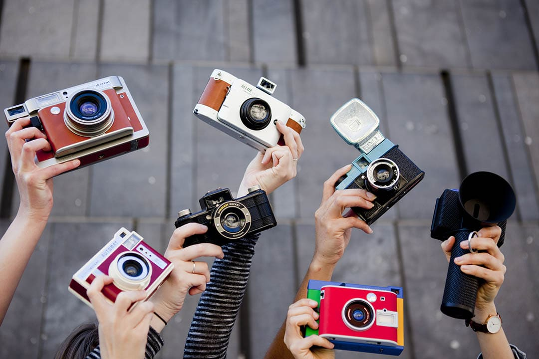 Hands holding up all the Lomography cameras