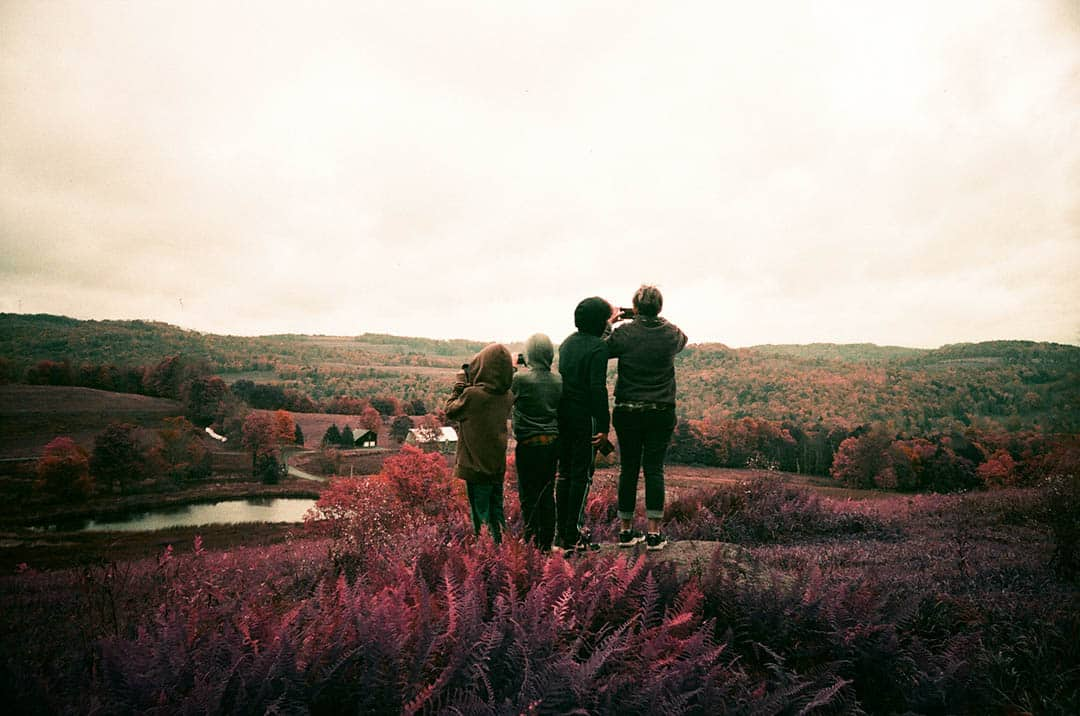 People standing on a hill watching the sunset. Image shot on Lomo Purple changes the green hues to appear red.