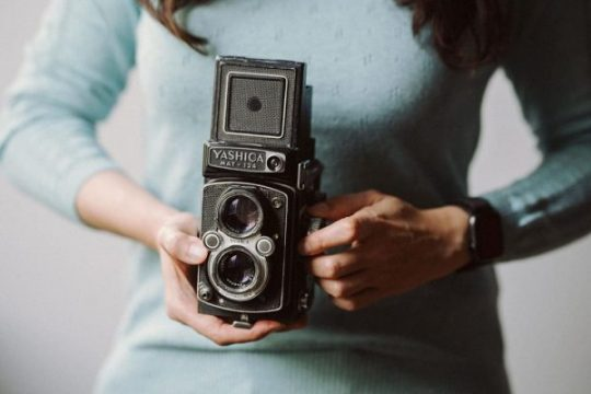 A photo of a woman holding a Yashica Mat 124